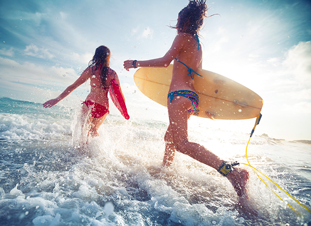 women running with surf boards